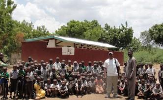 Deo, headmaster and pupils with Maendeleo toilet